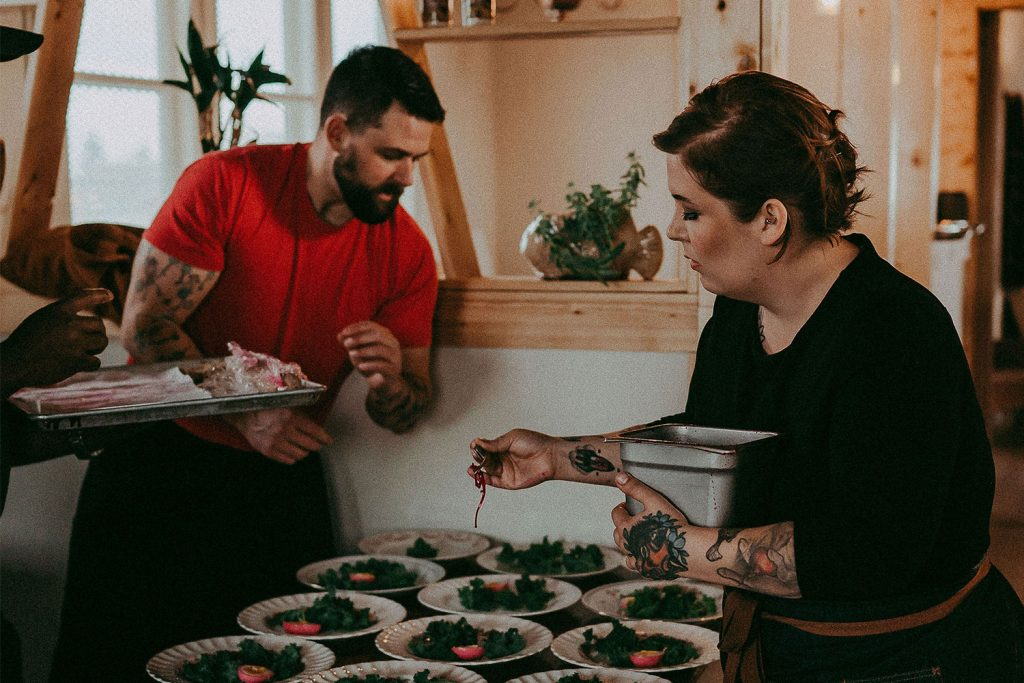 A man in a red shirt and a woman in a black shirt add finishing touches to food on white plates
