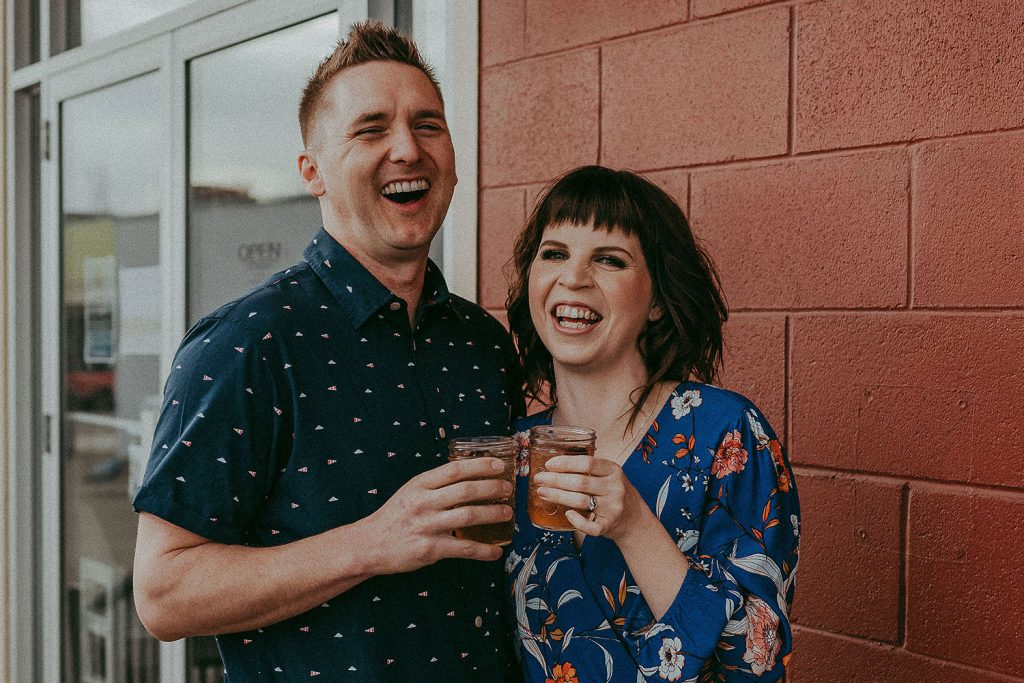 A happy couple cheers in front of a red brick wall