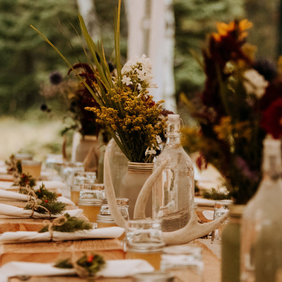 Fall flowers in white mason jars on a wooden table